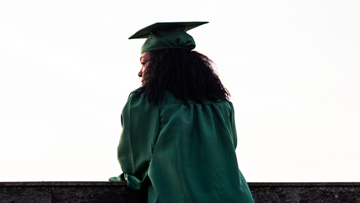 Girl standing in a green graduation cap and gown.