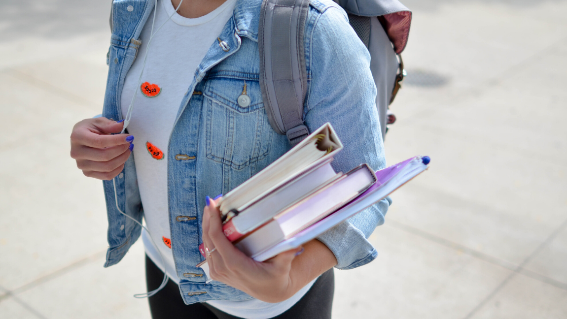 College student carrying books to class.
