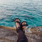 A person wearing strappy black sandals against the blue sea.