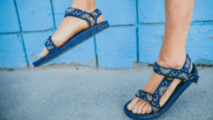 A person wearing a pair of blue Tevas with suns and moons on them with a blue wall in the background.