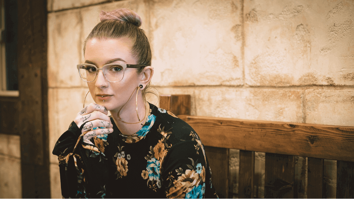 A woman wearing glasses looks into the camera.She has tattoos on her fingers.