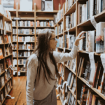 [a girl wearing glasses in standing between shelves at a library] Via Unsplash