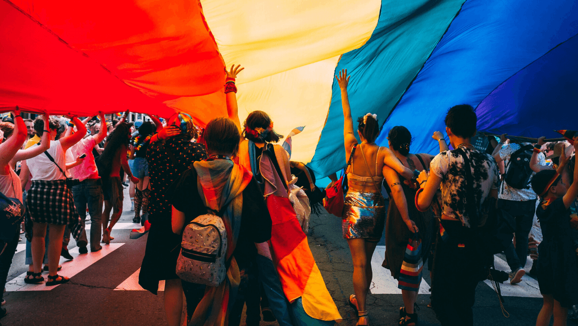 [A group of people adorned in pride-related clothing are walking underneath a pride flag] Via Unsplash