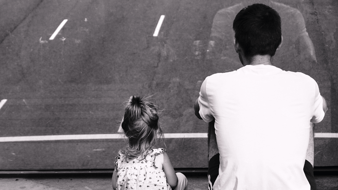 [A father a daughter sit near a street with their backs facing the camera. The image is in grayscale.] Via Unsplash