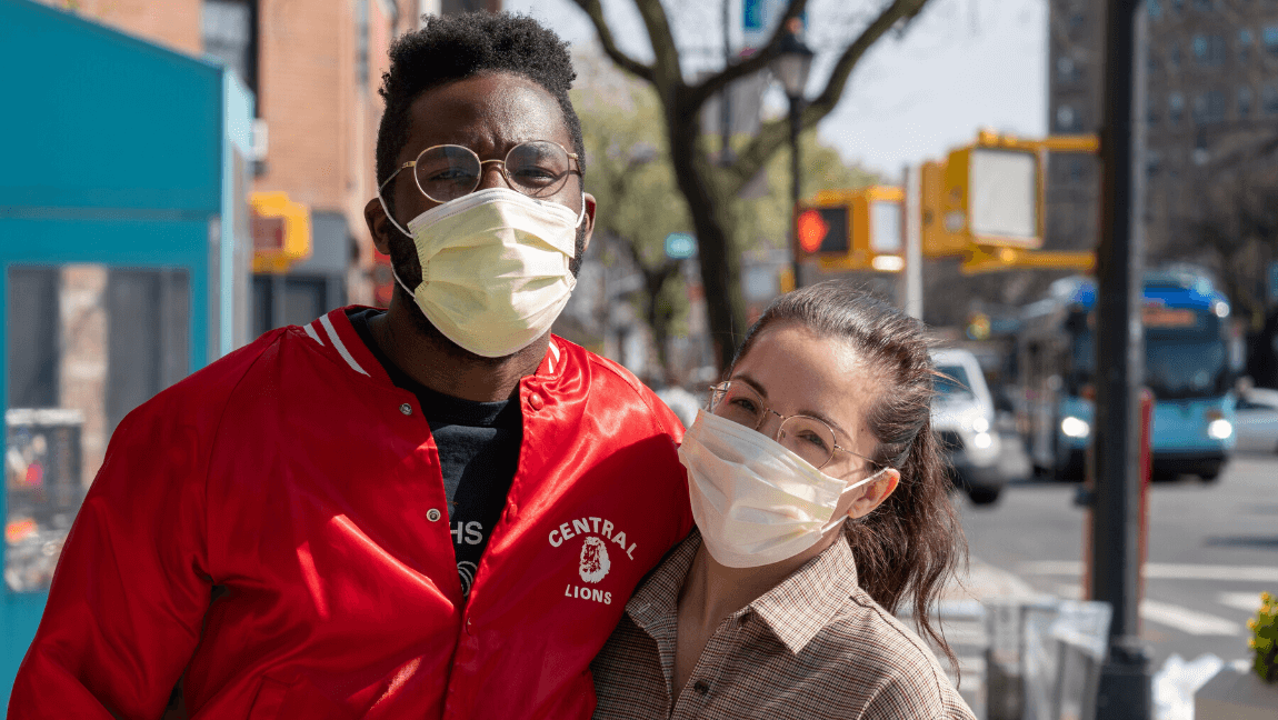 [Two people pose for a photo while wearing surgical masks] Via Unsplash