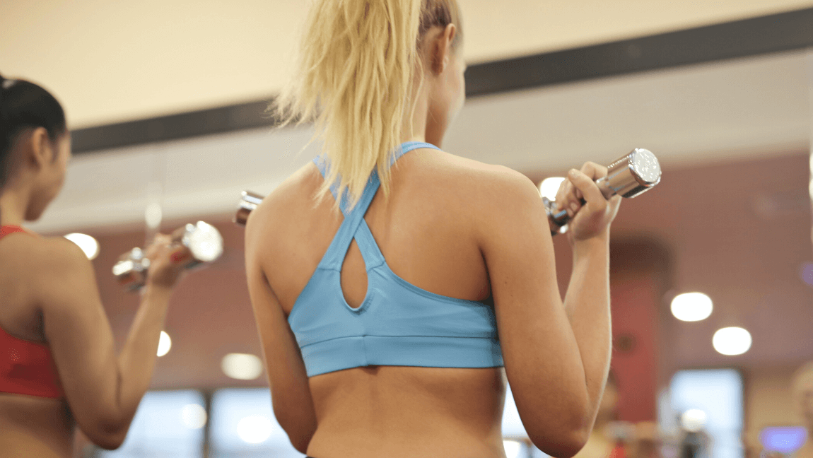 A girl with blonde hair and wearing a baby blue sports bra is lifting weights in front of a mirror.