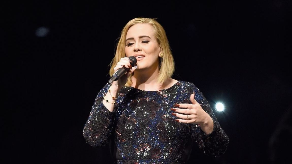 [Image description: Adele with a shiny dress singing against a black background.] Via Getty.