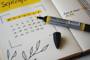 [Image Description: A bullet journal calendar with a yellow pen laying on it.] Photo by Estée Janssens on Unsplash