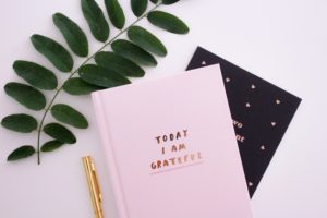 "[Image Description: A pink notebook with the words, ""Today I am grateful"" on it.] Photo by Gabrielle Henderson on Unsplash"
