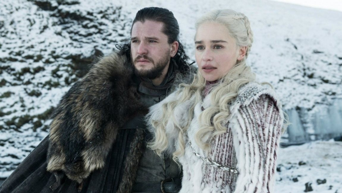 [Image description: Jon Snow and Daenerys dressed with big coats and standing in the snow. ] via HBO.