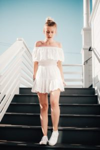 [Image Description: A woman stands in a white romper on stairs.] Photo by gbarkz on Unsplash