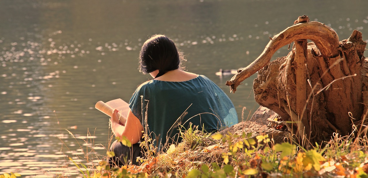 [Image Description: A girl with a book in her hand reads it by a lake.] via Pixabay