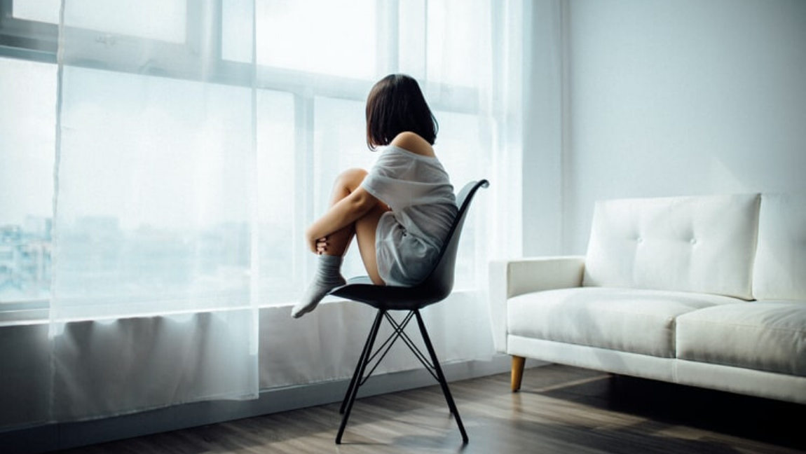 [Image Description: A girl is sitting on a black chair, with her back to the camera. She is looking out of a window] Via Unsplash