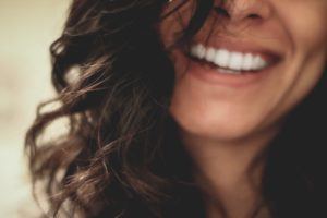[Image Description: A long brown-haired woman smiles at the camera.] Photo by Lesly Juarez on Unsplash