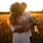 A couple kissing on a field. The woman is wearing a wedding dress, a flower crown and carrying a bouquet.