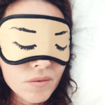 [Image description: A head that's partially covered by a sleep mask lays on a white pillow.] via reshot