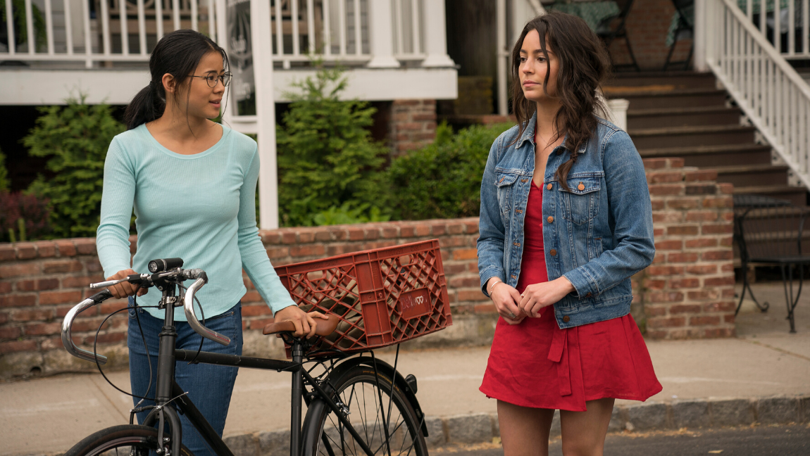 "[Image Description: Still from ""The Half Of It."" A still from ""The Half Of It"". Two girls walk side by side. One of them looks at the other, while the second girl gazes ahead] Via Netflix"