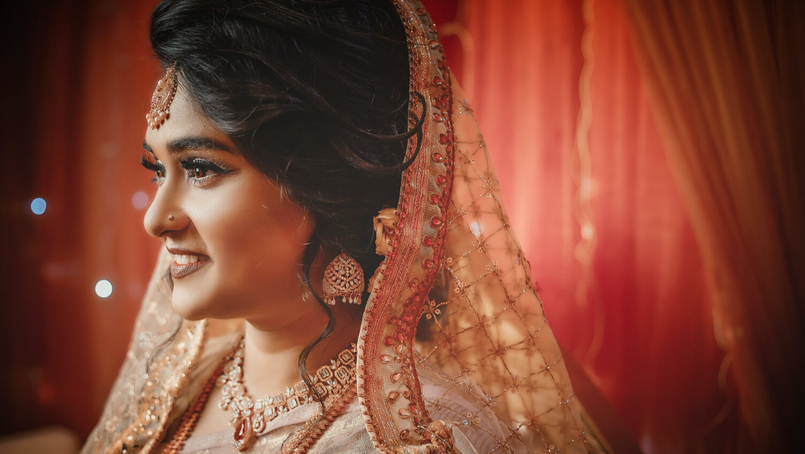 A South Asian bride smiles on her wedding day.