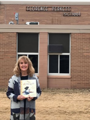 Attribution: [ Aya's teacher posing with a copy of her book in front of her elementary school]