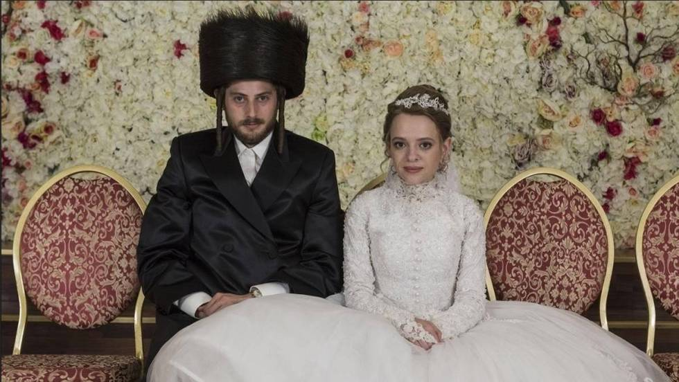 [Etsy's and Amit on their wedding. They are sitting down. Etsy wears a big white wedding dress and Amit a black coat and a big black hat.] Via Anika Molnar on Netflix.