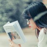 [Image description: woman with glasses reading a book.] via Min An on Pexels.