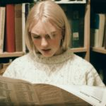 [Image Description: a blonde woman with a white sweater reading a newspaper in a library] Via Masha Raymers on Pexel