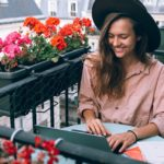 [Image Description: A woman with a black hat sitting in a balcony decorated with red flowers smiling and typing on her laptop ] via Daria Shevtsova on Pexels.