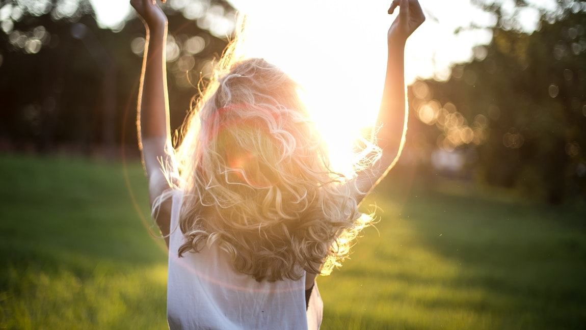 [Image description: A woman facing the sun, lifting up her arms.] Via Garon Piceli on Pexels