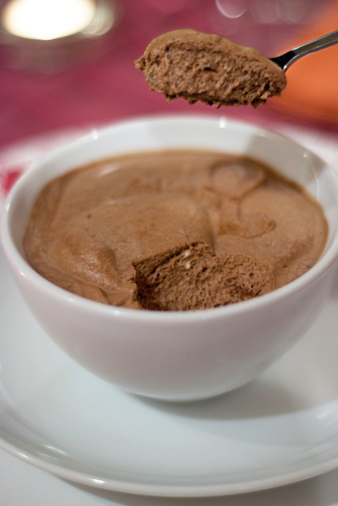 Bowl of chocolate mousse with someone taking a spoonful out
