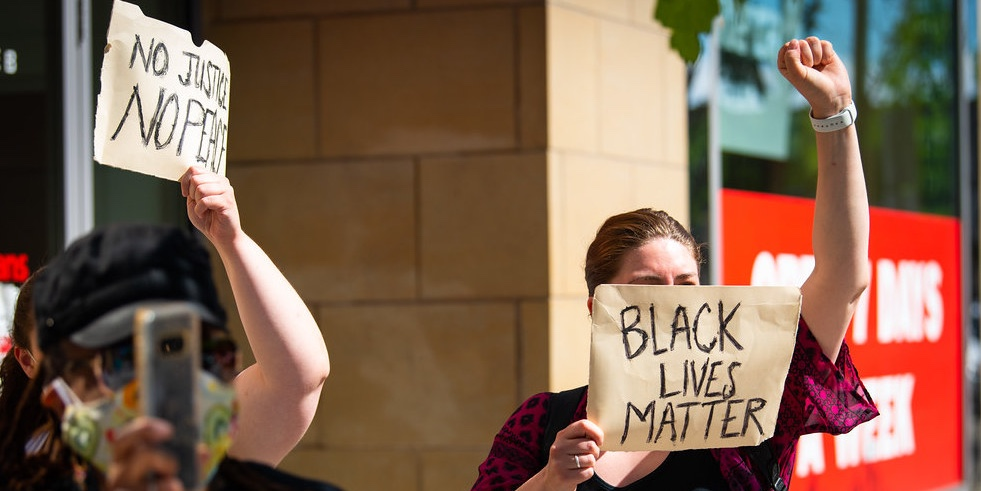A woman has a sign with the words 'Black Lives Matter' printed on it that covers her face via Unsplash