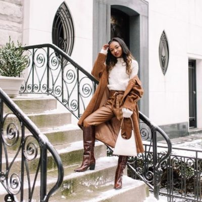 Black woman posing on a set of stairs, wearing a copper colored outfit
