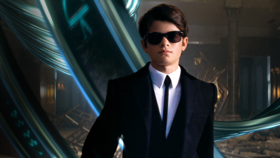 [Image Description: Artemis Fowl, a white boy with shaggy brunette hair and dressed in a black suit and dark black sunglasses struts towards the screen]. Via Disney.