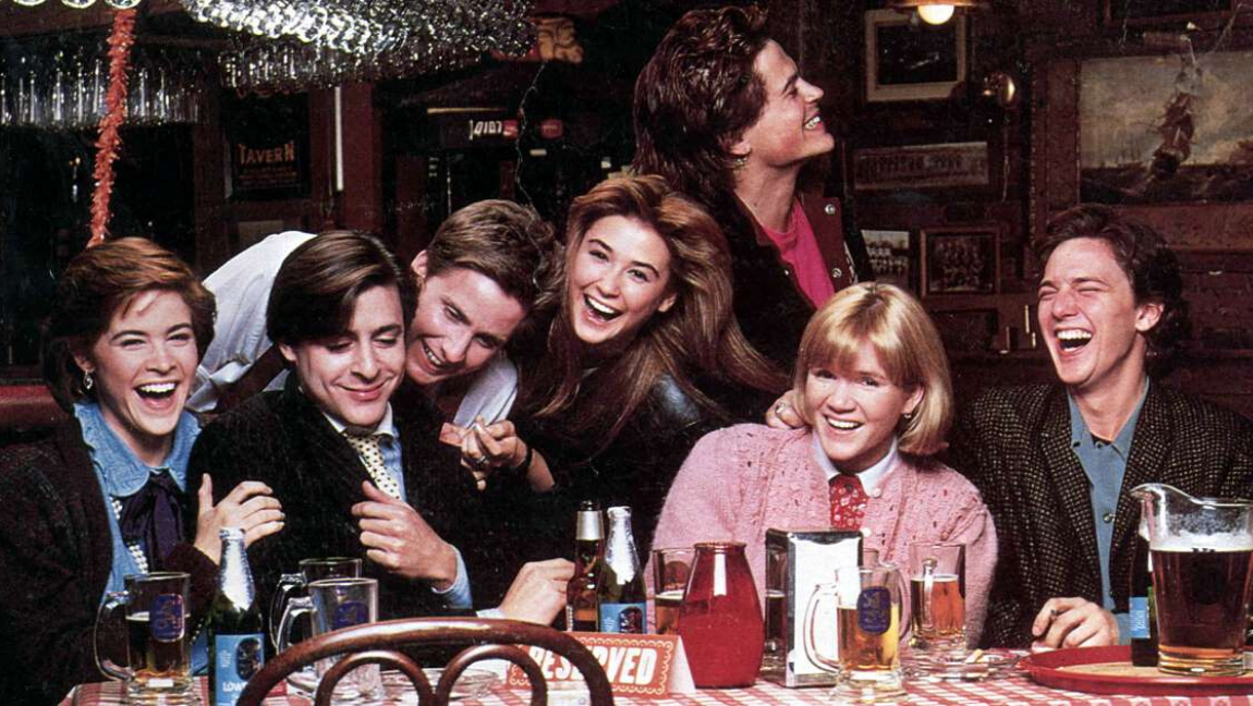 A group of young men and women sit at a table together laughing. There are drinks scattered across the table and a 'Reserved' sign.