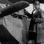 Bessie Coleman stands on the wheel of a plane.