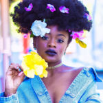 Black woman wearing denim dress with flowers on hair