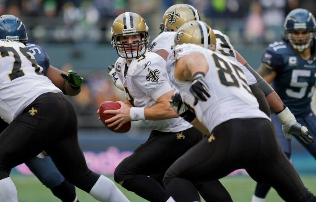 Drew Brees backs up holding the ball, ready to pass to a teammate.