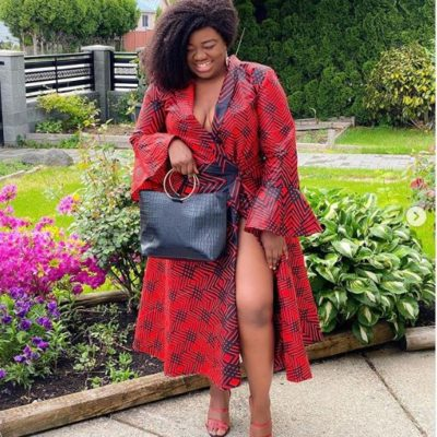 Ajibe Oge wearing a red jacket dress with a black oversized purse