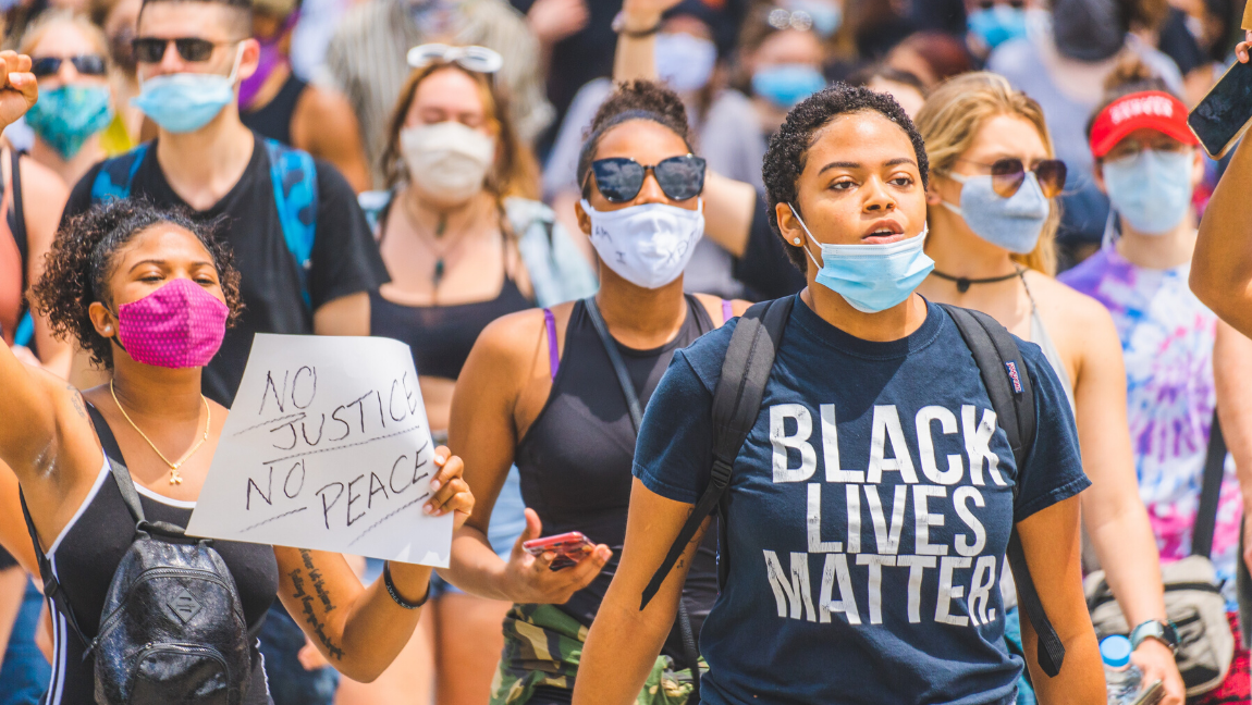 [Image Description: A young woman wearing a mask and black lives matter t-shirt marching in a #BlackLivesMatter public demonstration in Cincinnati.]