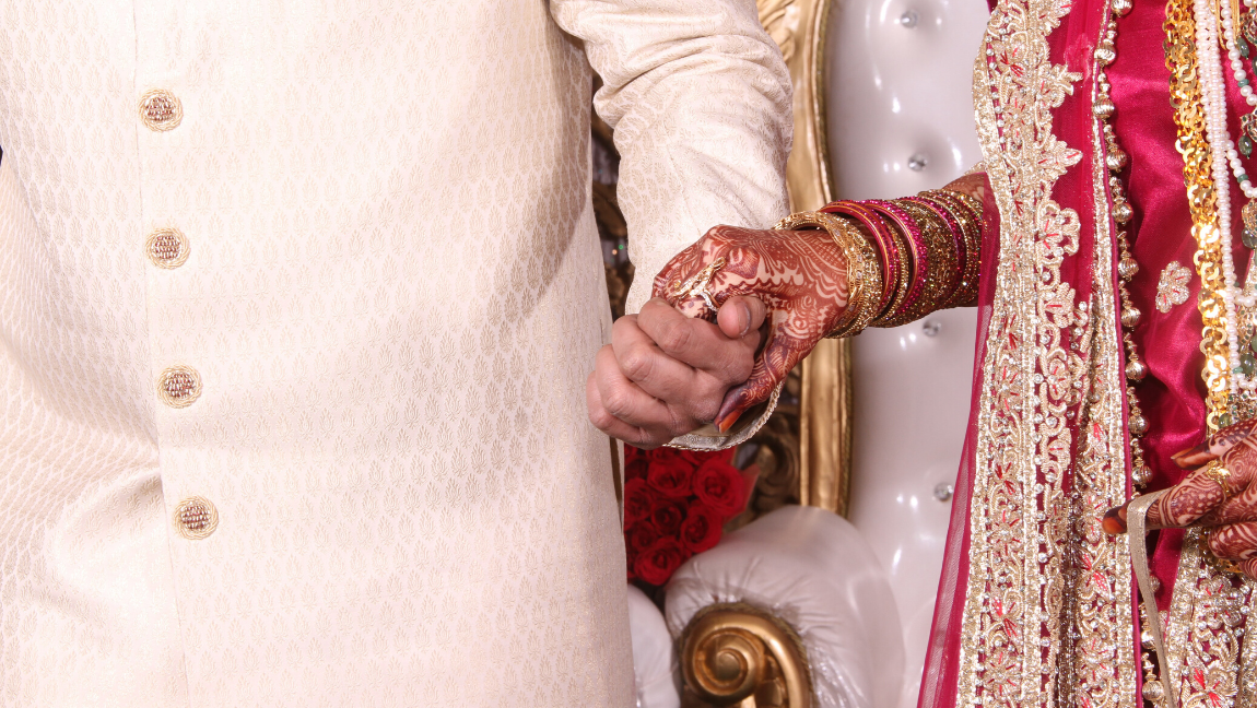 [Image Description: A close up a bride and grooms hands at a wedding ceremony.] Via Unsplash