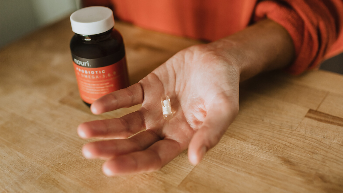 A woman holds a probiotic in her hand.