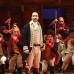 [Image Description: A group of men on a stage dressed as eighteenth-century soldiers.] Via Disney+