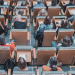 Students sit in a lecture hall, facing the front of the room. Via Unsplash