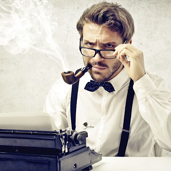 A man with a stern expression sits in front of a typewriter, smoking a pipe.