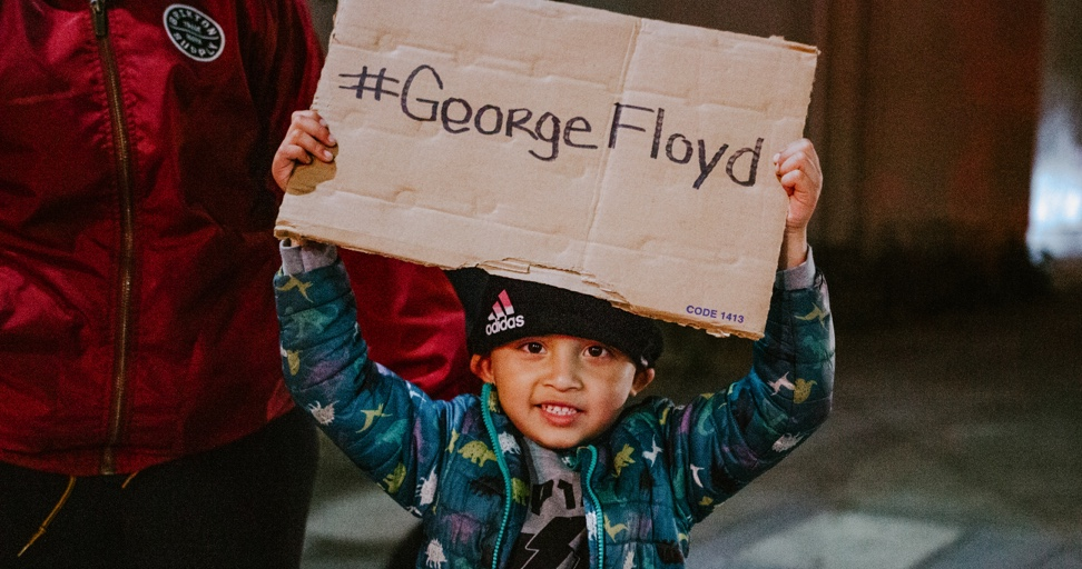 A child holds up a sign with the words #GeorgeFloyd printed on it