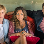 """[Image Description: still from """"Lovrsick"""": three friends - a blond man, a woman with long blonde hair, and a white brunette man in a sport jacket - sit together on a red couch]. Via Netflix."""