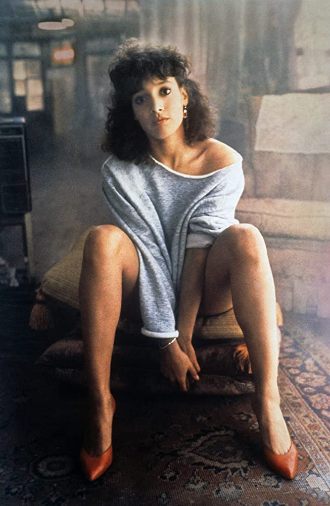 Still from 'Flashdance' (1983). A young woman sits on a stack of cushions wearing a gray oversized sweater that exposes her shoulder.