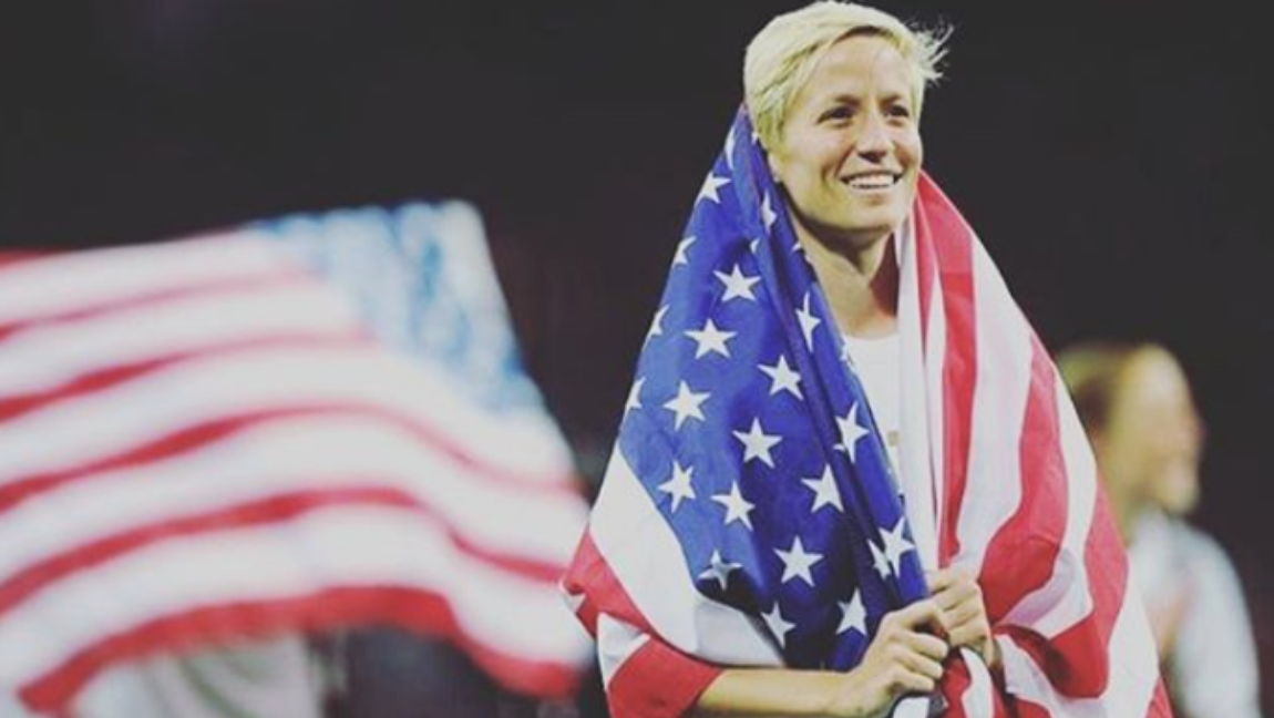 [Image description: A tall white woman with a blonde pixie cut drapes herself in the American flag in celebration.] Via Instagram / @mrapinoe.