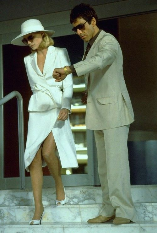 A woman wearing a white skirt suit, shoes, hat, and sunglasses walks down a flight of stairs with a man wearing dark glasses and checking his watch.