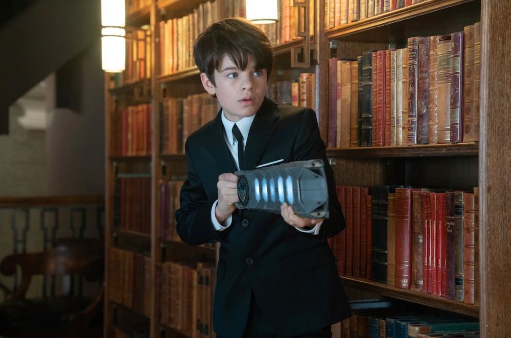 [Image Description: A young white boy with shaggy brunette hair cautiously creeps through the library towards something offscreen while holding a magic gun-like weapon]. Via Disney.