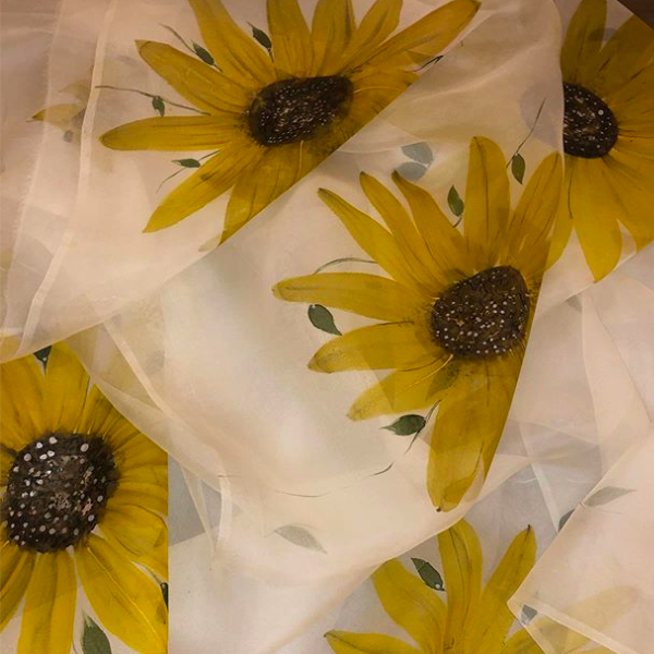 Sunflowers painted on a plain white fabric.